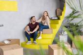 selektiver Fokus des fröhlichen Paares, das auf gelben Treppen in der Nähe von Kartons sitzt, bewegtes Konzept