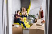selektiver Fokus junger Frauen und Männer, die auf Treppen in der Nähe von Boxen sitzen, Verlagerungskonzept