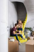selektiver Fokus junger Paare, die auf Treppen in der Nähe von Boxen sitzen, Verlagerungskonzept