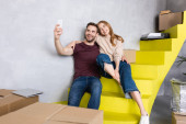 Photo excited couple sitting on yellow stairs and taking selfie near carton boxes