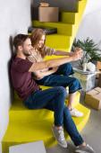 joyful couple sitting on yellow stairs and taking selfie near carton boxes