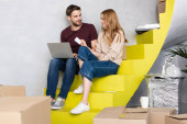 selective focus of man with laptop looking at girlfriend holding credit card while sitting on stairs