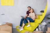 Mann sitzt auf Treppe neben Frau mit Kreditkarte in der Nähe von Laptop und Kisten