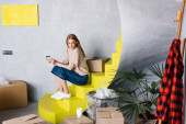 young woman holding credit card and sitting on stairs near boxes