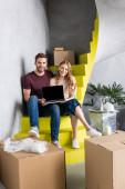 freudiges Paar hält Laptop mit leerem Bildschirm, während es auf Treppen in der Nähe von Boxen sitzt, Umzugskonzept