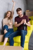 man opening bottle while pleased young woman holding glasses and sitting on stairs, moving concept