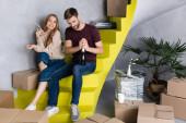 muž otevírání láhev zatímco potěšený přítelkyně drží brýle a sedí na schodech, pohybující se koncept
