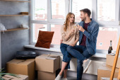 pleased man hugging girlfriend and clinking glasses with champagne near carton boxes, moving concept