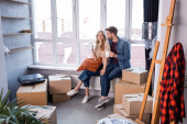 pleased couple holding cups of tea near carton boxes, moving concept