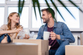 selective focus of joyful woman holding cup and unpacking box with boyfriend, moving concept