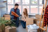 freudiger Mann hält Kissen neben Frau beim Auspacken von Kisten, bewegendes Konzept