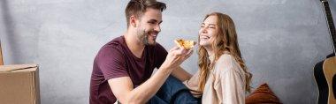 Horizontal image of joyful man holding delicious pizza near girlfriend stock vector