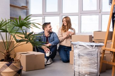 Man and woman holding cups and looking at each other while unpacking carton boxes in new home stock vector