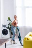 Moderní hospodyňka s vysavačem při pohledu na kameru v blízkosti rostlin a pračky