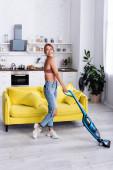 Hausfrau schaut weg, während sie Boden mit Staubsauger putzt