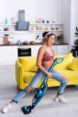 Hausfrau mit Staubsauger imitiert Gitarrenspiel in der Nähe der gelben Couch