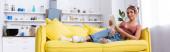 Panoramatický záběr ženy s digitálním tabletem ležící na gauči