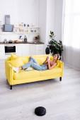 Frau liegt auf Couch und nutzt Smartphone