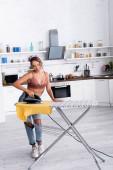 Fiatal háziasszony vasaló póló vasalódeszka a konyhában