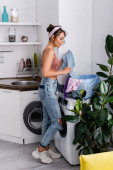 Seitenansicht der Hausfrau, die Kleidung aus dem Wäschekorb neben der Waschmaschine in der Küche nimmt
