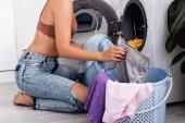 Fotografie Ausgeschnittene Ansicht einer jungen Hausfrau, die während der Hausarbeit Kleidung in der Nähe der Waschmaschine hält