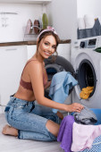 Brünette hausfrau looking at camera während putting kleidung in waschmaschine