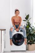 Fotografie Barfüßige Hausfrau blickt in die Kamera, während sie auf der Waschmaschine sitzt