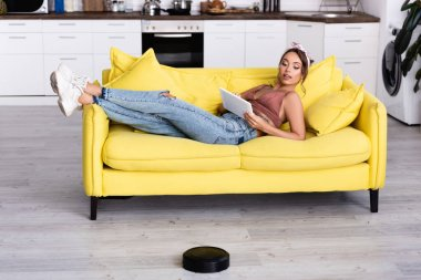 Woman on couch with digital tablet and robotic vacuum cleaner at home