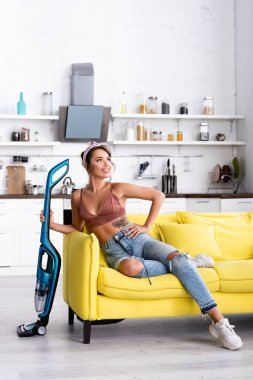 Housewife with hand on hip looking away and holding vacuum cleaner