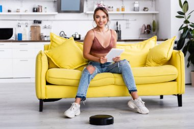 Woman sitting and looking at camera near robotic vacuum cleaner stock vector