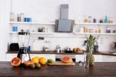 Čerstvé ovoce na řezací desce u skla a mixéru na kuchyňském stole