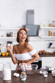 Selective focus of young woman holding eggs near flour while cooking at home
