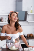 Selektiver Fokus tätowierter Hausfrau beim Kochen zu Hause beim Mischen von Zutaten