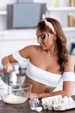 Selective focus of brunette housewife using mixer while cooking near eggs at home stock vector