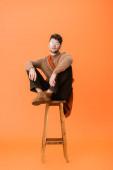 Stylischer Mann im Herbst-Outfit und Brille auf Holzhocker sitzend und in die Kamera blickend auf orange