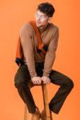 Fotografie Stilvoller Mann im Herbst-Outfit und Brille auf Holzhocker sitzend und isoliert auf orange schauend