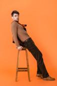 Stylischer Mann im Herbst-Outfit und Brille auf Holzhocker in Orange gestützt