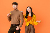 trendy couple in glasses and autumn outfit holding apples isolated on orange