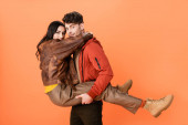 trendy man holding in arms woman in autumn outfit on orange