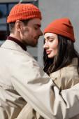 stylový pár se zavřenýma očima v pláštích a kloboucích