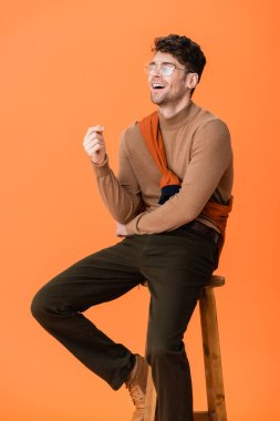 Excited man in autumn outfit and glasses sitting on wooden stool and laughing on orange stock vector