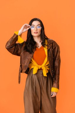 Young woman in autumn outfit looking at camera and touching glasses isolated on orange stock vector