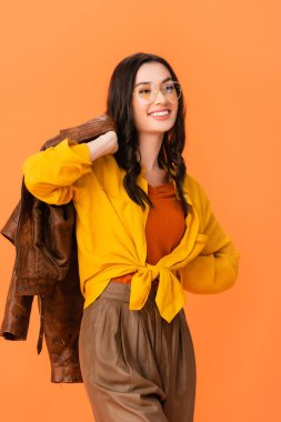 Trendy woman in glasses and autumn outfit holding leather jacket while standing with hand on hip isolated on orange stock vector