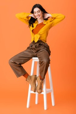 Full length of trendy woman in autumn outfit and boots sitting on white stool and looking down on orange stock vector