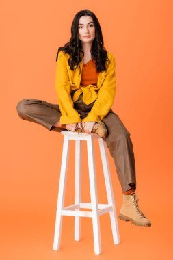 Full length of fashionable woman in autumn outfit sitting on white stool and looking at camera on orange stock vector