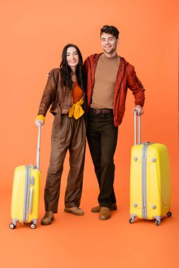 Full length of stylish couple in autumn outfit standing near yellow baggage on orange stock vector