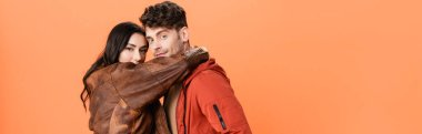 Horizontal crop of brunette woman hugging stylish man isolated on orange stock vector