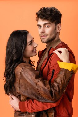 Young brunette woman hugging stylish man in jacket isolated on orange stock vector