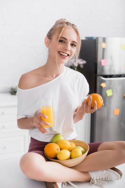 Young blonde woman sitting on kitchen table with orange juice and fresh fruits stock vector