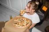 vysoký úhel pohledu na mladé blondýny žena jíst pizzu, zatímco sedí na podlaze v kuchyni